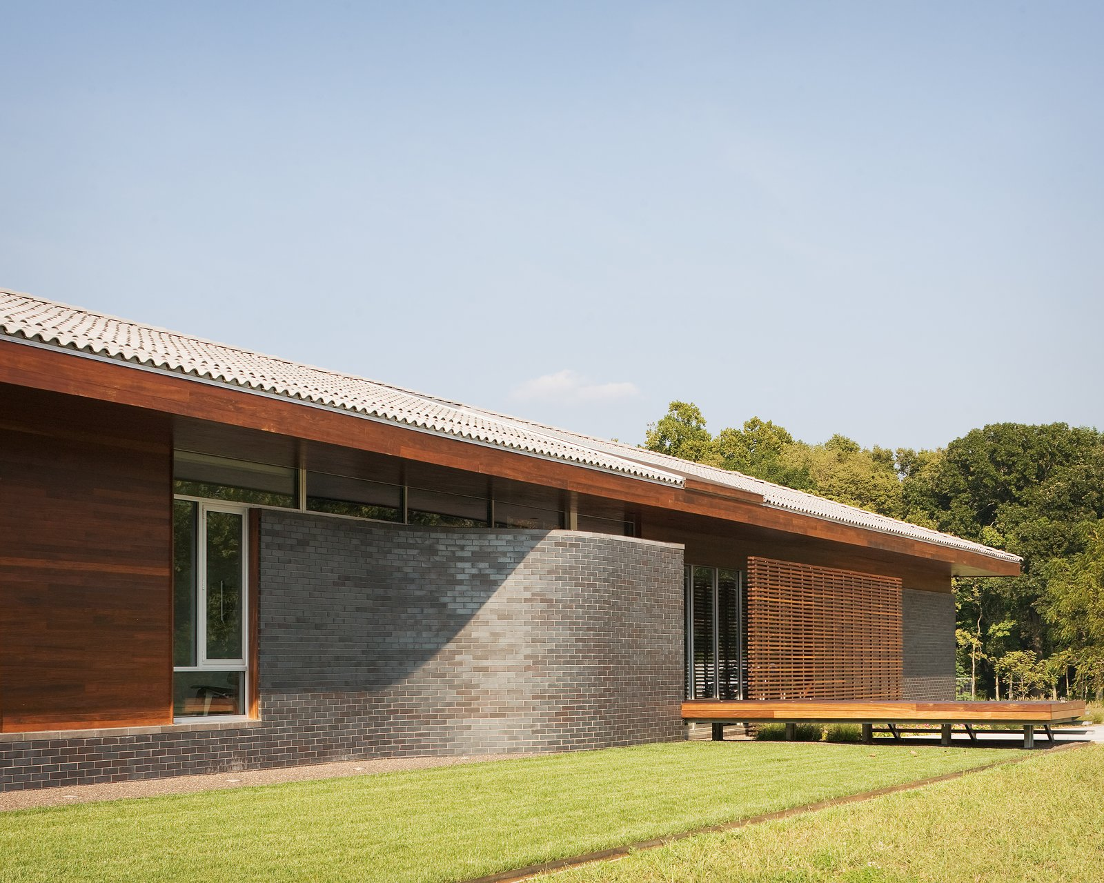 The firm chose Endicott brick for the curved elements of the exterior, a natural material with a glossy effect that creates the illusion of changing colors and animated movement. The dark grey contrasts boldly with the earthy brown tones of the durable ipe wood used for the exterior walls.  Brick Houses from Around the World  by Matthew Keeshin from A Bold Home Creatively Combines Curves and Modern Lines
