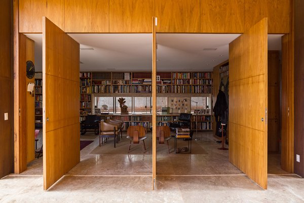The library's entrance features massive panel doors made of tropical freijó wood. Inside, leather armchairs by Jorge Zalszupin accent the space.