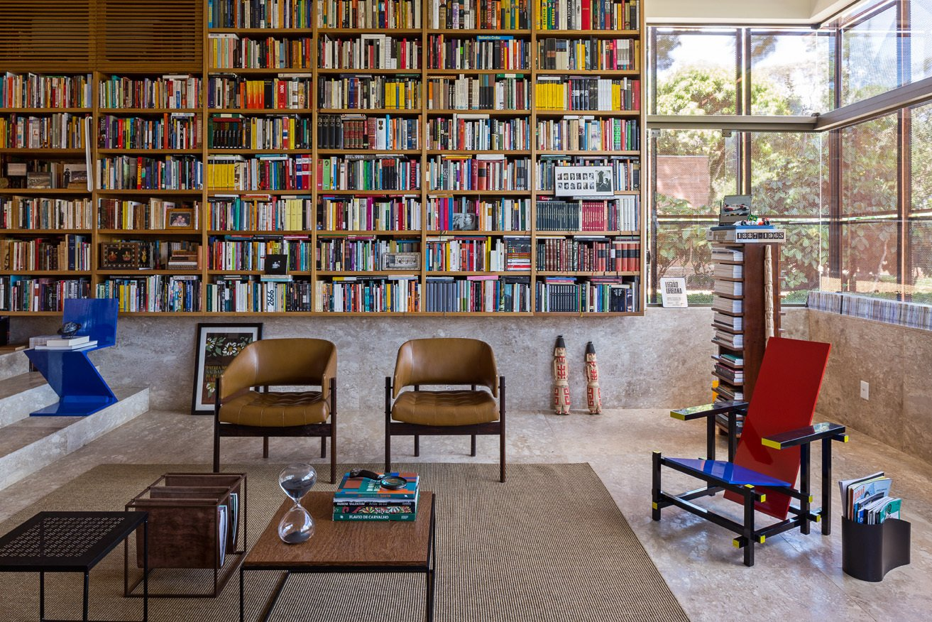 "Office, Chair, Shelves, Bookcase, Rug Floor, and Library Room Type Architect Gustavo Costa calls the home library the ""project's heart."" This central space houses the owner's expansive collection of about 5,000 books, and acts as a meeting place for friends and colleagues. A Gerrit Thomas Rietveld Red and Blue chair completes the space.  30+ Modern Homes With Libraries by Matthew Keeshin from House of the Week: Indoor-Outdoor Brazilian Modern Home"