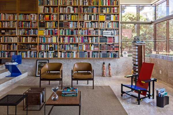 "Architect Gustavo Costa calls the home library the ""project's heart."" This central space houses the owner's expansive collection of about 5,000 books, and acts as a meeting place for friends and colleagues. A Gerrit Thomas Rietveld Red and Blue chair completes the space."