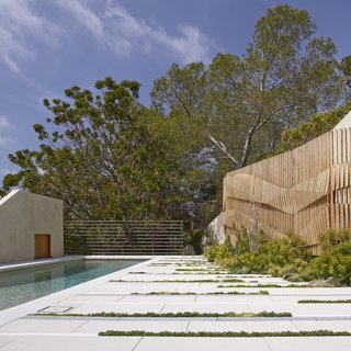 """Concealing a stair leading to trail access to the park, the wall's form suggests the folds and striations of the sandstone geology,"" explains SurfaceDesign. While the wall and fence provide more privacy for the backyard, their transparency restores visual connections with the park."