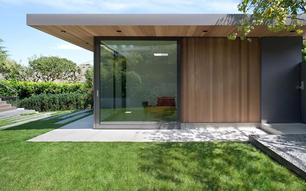 """Before, the house turned its back on the landscape,"" said Parish. ""This renovation and addition really animates the garden."" Sliding glass doors match those of the living room beyond the deck, and both can be completely open to the yard."