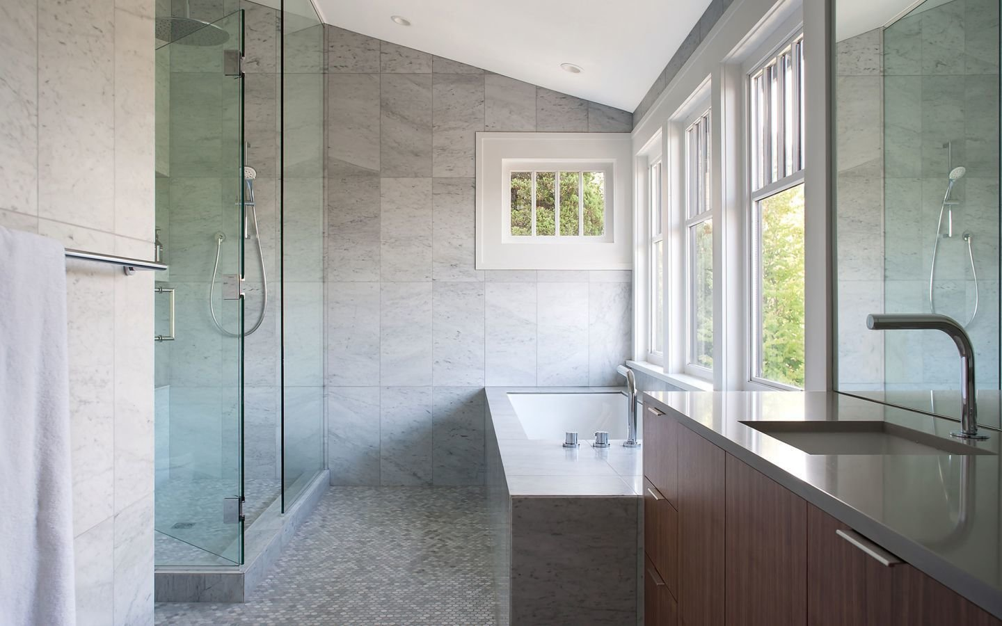 Bath Room, Engineered Quartz Counter, Marble Floor, Undermount Sink, Soaking Tub, Drop In Tub, Enclosed Shower, and Marble Wall Interior walls were repainted and flooring was repaired, but the master bathroom received the most attention in the existing house. The renovation included marble mosaic floor tiles, fixtures by Blu Bathworks, and Silestone countertops.  Photo 7 of 8 in A Vancouver Renovation Transforms a Backyard Into a Giant Living Room from A Vancouver Renovation Transforms a Backyard into a Giant Living Room