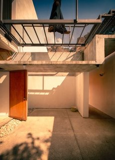 A mesh steel bridge sits above a cast concrete outdoor canopy on the patio. Concrete floors are polished on the inside, and kept rough on the outside. A pine door leading to a lower level bedroom adds warmth.