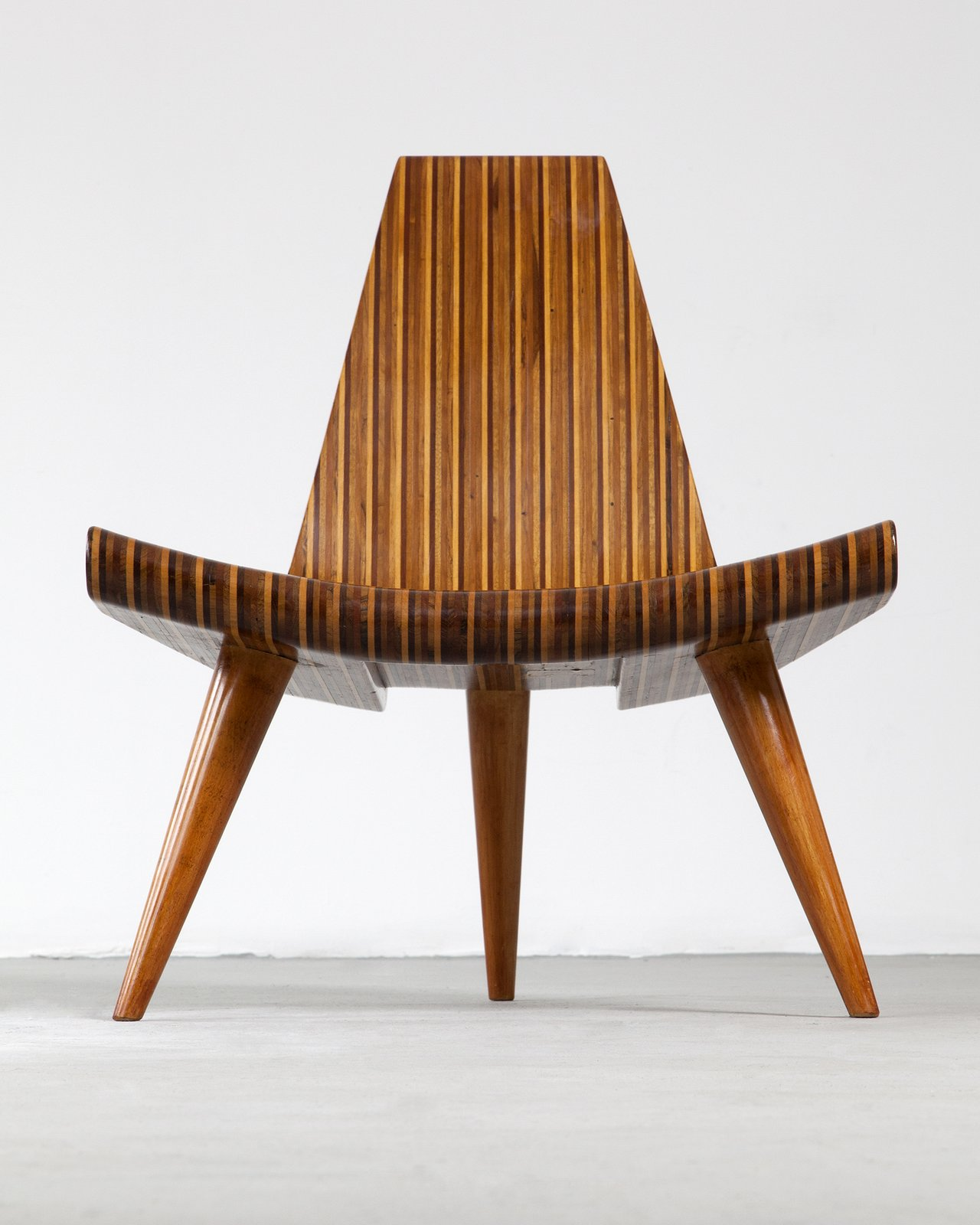 Widely consider the first modern master of Brazilian design, Joaquim Tenreiro created many timeless classics. His contribution to Brazilian design is evident by his designs that made hardwood furniture sleeker and lighter. Tenreiro's 1947 Three-Legged chair was laminated in multiple woods that included native species such as imbuia, roxinho, jacaranda, ivory, and cabreúa. In this example, the chair is made in five different types of hard wood, with bonded laminated. The chair celebrates the material with its inventive form and combinations of wood.  100+ Best Modern Seating Designs from Bring the Best of Brazilian Modernism to Your Home with This New Book