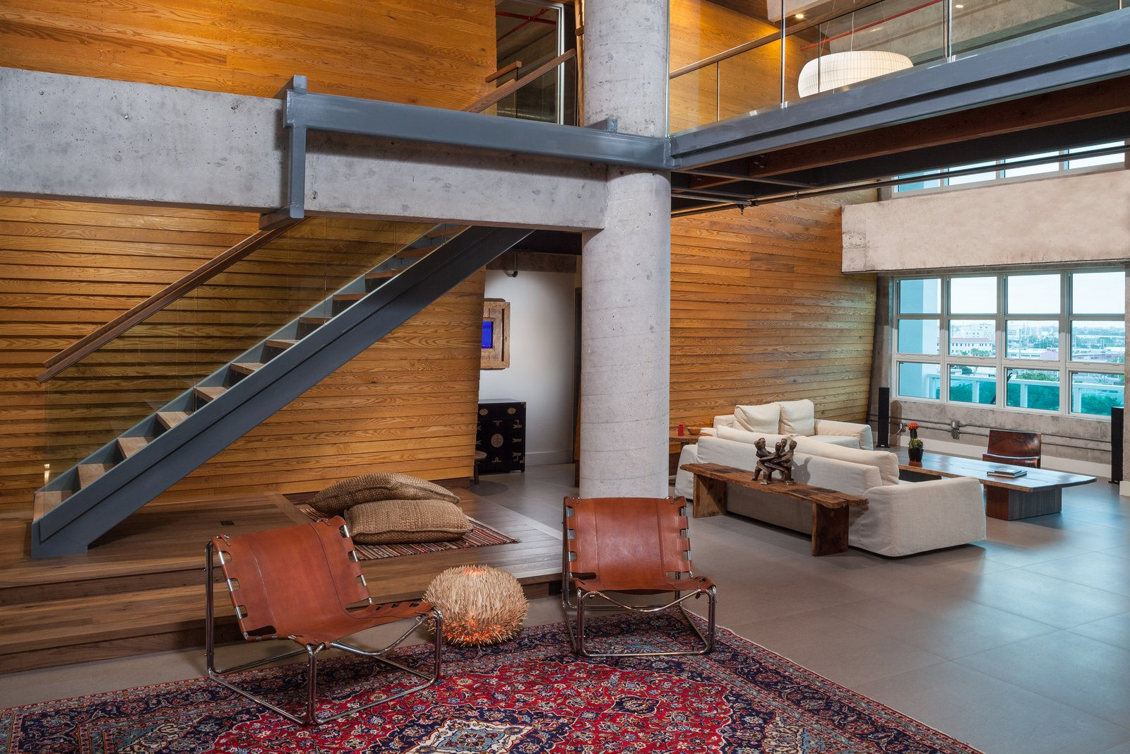 Living Room, Chair, and Ottomans The warped wooden wall backing the living room not only visually counterbalances the coldness of the steel and glass, but also reduces reverbation throughout the entire loft.  Photo 1 of 7 in A Miami Renovation That Blends Concrete and Rich Wooden Interiors