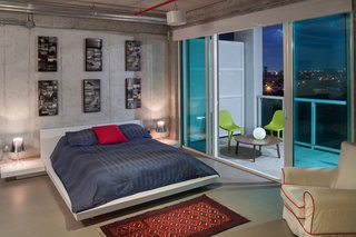 Balcony views and large sliding glass doors add to the tranquil airiness of the master bedoom.