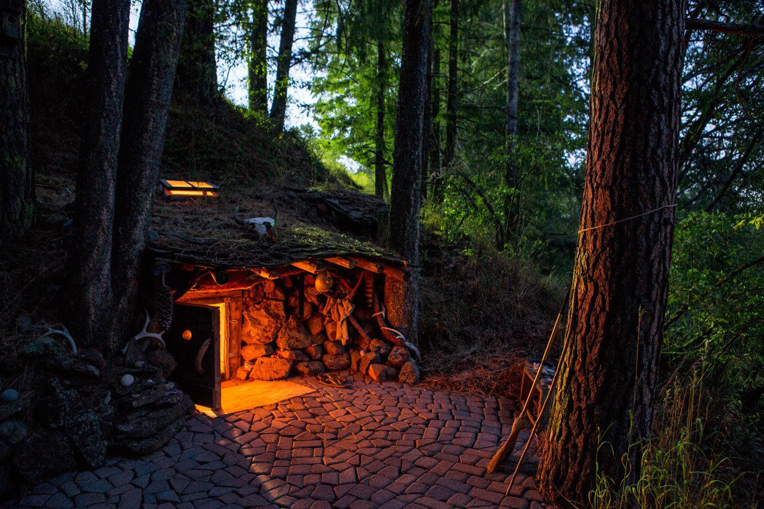 Some cabins are underground, or in the book's taxonomy, Earthen. Dan Price's former home was once broken into and the result was his commitment to live with fewer things, in nature. His hobbit-like home in Joseph, Oregon is complete with tunnels, crawlspaces, and a low-ceilinged bedroom. Using heavy-guage sheeting and wooden structures as roofing elements, he covered the space with dirt to facilitate natural growth above.  Daring Hillside Homes by Diana Budds
