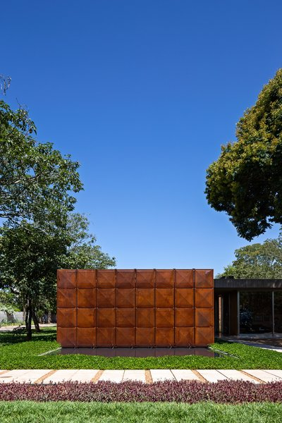 The geometric front facade of the home is made of Cor-Ten steel, segregated into eight vertical panels. Juxtaposed with its lush natural environment, the front elevation is a minimal and abstract counterpoint to its surroundings. An exterior pool meets the facade at its base.