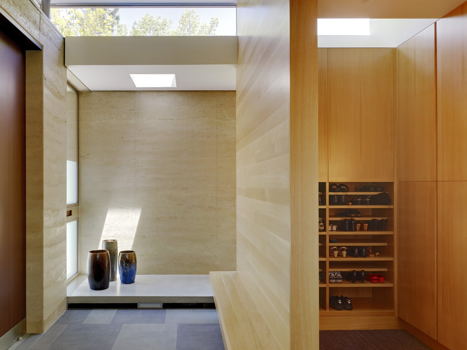 A traditional genkan (a Japanese entryway) was part of the architectural program early on. Shoes are removed before entering the main living space, which is elevated six inches above the floor level of the entryway. The blonde wood is rift-cut white oak.  Photo 6 of 11 in 11 Ways to Create a Modern Mudroom in Your Home from Designs Inspired by Japanese Architecture and Craft
