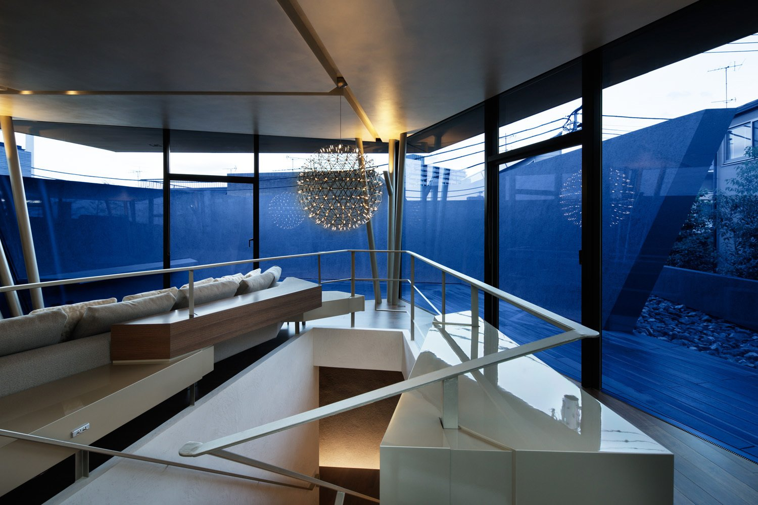 A Raimond by Moooi pendant light fixture hangs over the staircase , while angular railing emphasizes the spiral-esque floor plan.  SRK by Caroline Wallis
