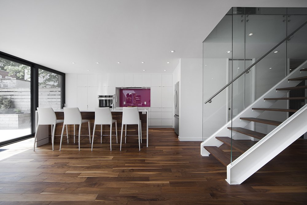 "The white kitchen matches the clean aesthetic of the rest of the home, but the team at Blouin Tardif agreed that it needed an unexpected element of color. The fuchsia backsplash by Lacobel adds what Blouin refers to as a ""funky"" quality.  190+ Best Modern Staircase Ideas from A Montreal Duplex Is Transformed Into An Elegantly Simple Light-Filled Home"