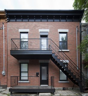 """At the city's request, the design at the front of the home did not receive a major change—which included keeping the duplex's stairs. """"Everything is restored, but in a way that is respectful,"""" Blouin said."""