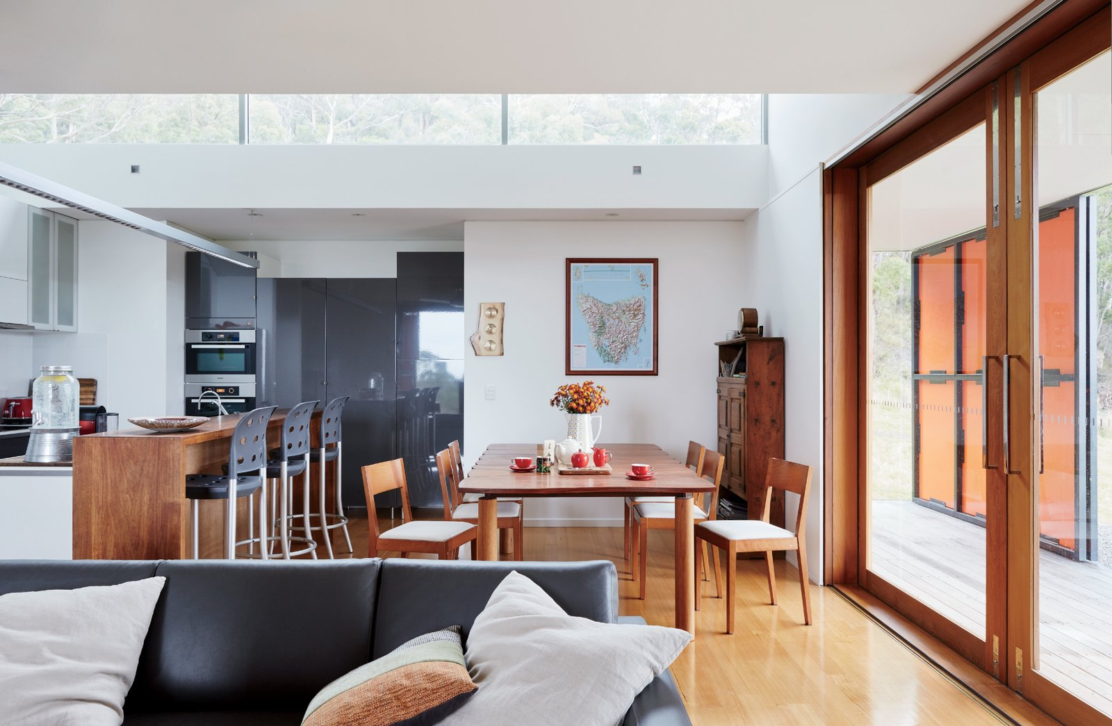 The Tasmanian blackwood dining table is by Mark Bishop, and the sofa is from King Furniture.  Photo 7 of 10 in An Off-the-Grid Prefab that Combines Open Plan Living with Rugged Durability