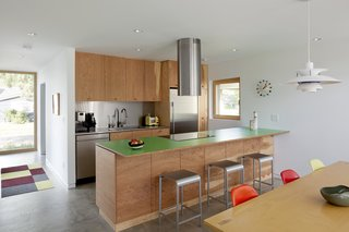 A green laminate countertop by Abet Laminati is surrounded by Norman Foster's Emeco 20-06 counter stools at the island in the kitchen, which has an integrated Frigidaire induction range, Faber Cylindra Isola range hood, Blomberg dishwasher, Fisher & Paykel fridge, and flat-grain fir plywood cabinets by Portland craftsman Doug Chamblin. A Louis Poulsen PH 5 pendant illuminates a Modernica Tenon Table and Eames Molded Plastic chairs with Eiffel bases. A George Nelson Ball Clock hangs nearby.