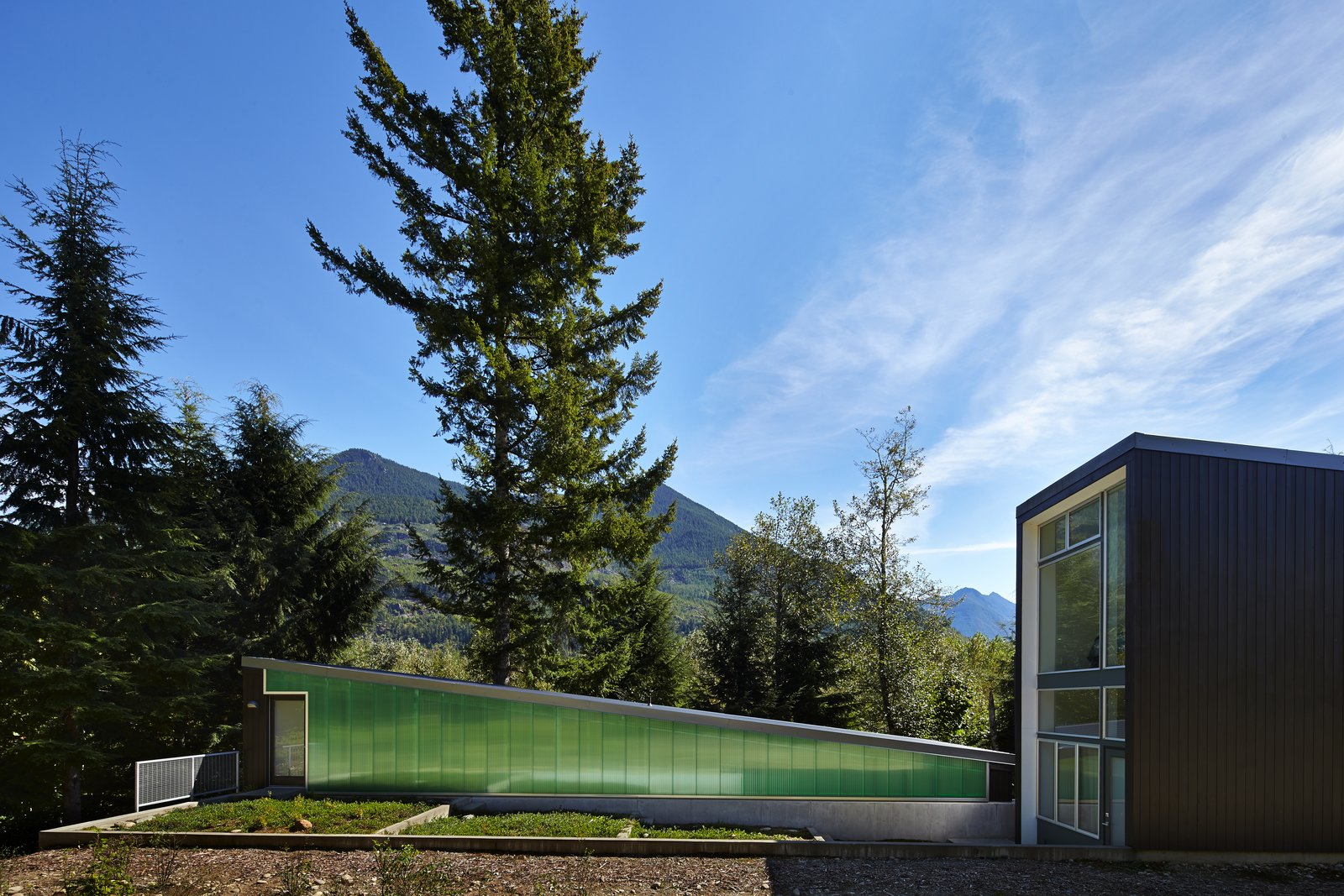 """A polycarbonate wall by Lexan Thermoclick colors the west side of the studio. Exterior doors are from Codel, and they are also painted in Benjamin Moore's """"dark pewter.""""  Photo 4 of 10 in This Retreat in the Cascades is a Bold Take on the Modern Cabin"""