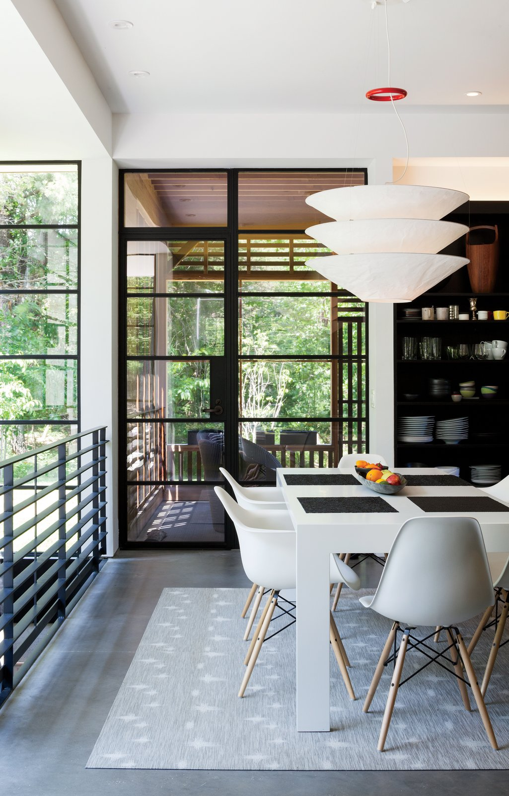 Dining Room, Table, Chair, Pendant Lighting, Rug Floor, and Shelves In the dining area are a Gamma table by Cappellini, Eames molded plastic chairs, and a Flotation pendant by Ingo Maurer.  Eames Molded Chairs from A Couple Takes an Unassuming Plot of Land and Calls it Home