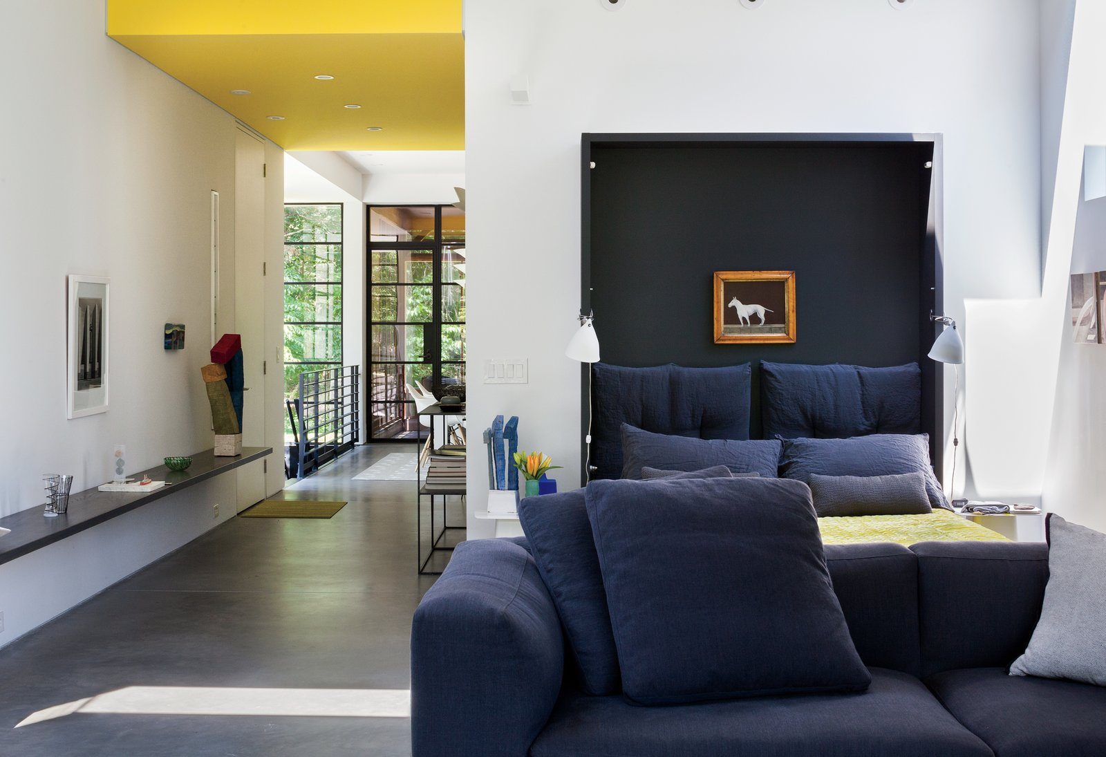 When folded down, deep navy-blue cushions give the effect of a lush headboard. While the home does not yet have a proper master bedroom, the couple plans to create an addition sometime next year.  Photo 5 of 11 in A Couple Takes an Unassuming Plot of Land and Calls it Home