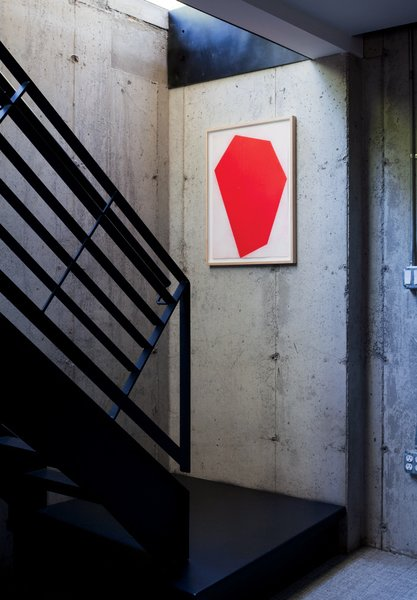 A red print by Cris Gianakos accents a well-lit stairwell leading to a laundry area, library, and rec room on the full basement floor.