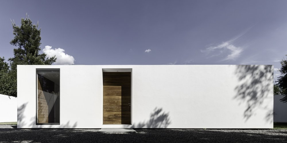 Both the white facades and modules' orientations are crucial in maintaining comfortable indoor temperatures. Designed with the sun path in mind, each part of the home shades the courtyard year-round for residents.  Photo 1 of 7 in A Minimalist Mexican Retreat Uses an Array of Strategies to Beat the Heat from A Minimalist Mexican Retreat that Uses an Array of Strategies to Beat the Heat