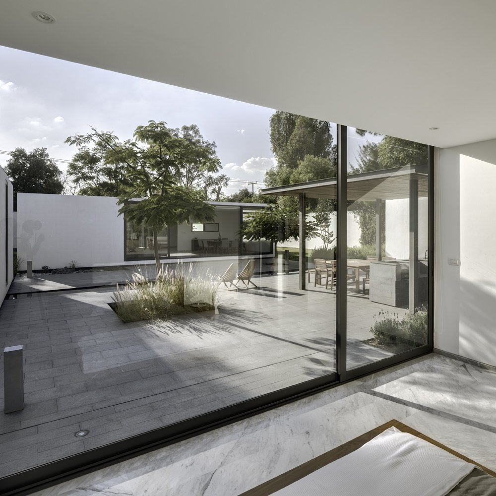 The interior marble flooring and exterior granite surfacing blend well to complement the spare white modules. Both materials were chosen with climate in mind: granite because it both absorbs less heat and is easy to clean, marble because it cools down the interior.  Photo 5 of 7 in A Minimalist Mexican Retreat Uses an Array of Strategies to Beat the Heat