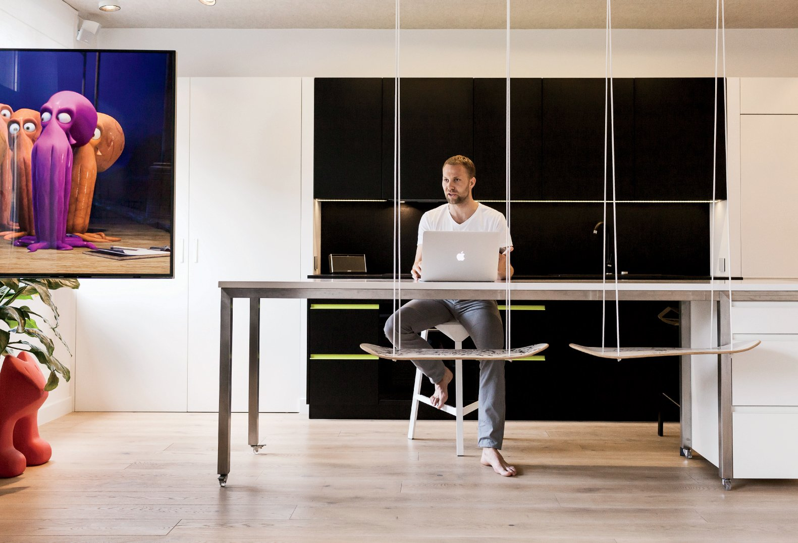 The kitchen island easily doubles as a desk.  Photo 4 of 12 in This Tiny Warsaw Studio Instantly Changes from Office to Playroom