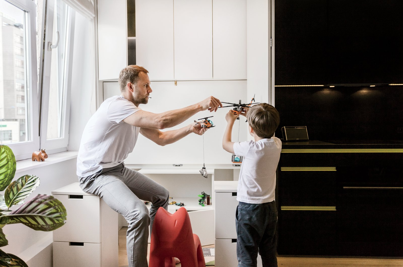 Behind two closed doors lies a custom fold-down desk with cabinets that store Bartek's toys when he's not at the apartment.  Photo 5 of 12 in This Tiny Warsaw Studio Instantly Changes from Office to Playroom