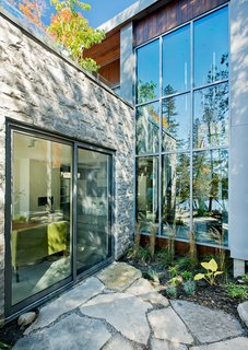 "While the homeowners and their guests have plenty of opportunities to view the outdoors, thanks in large part to windows and doors by Alumilex, an abundance of cedars offers privacy from the outside looking in. ""We wanted to cut the least amount of trees,"" Tremblay said."