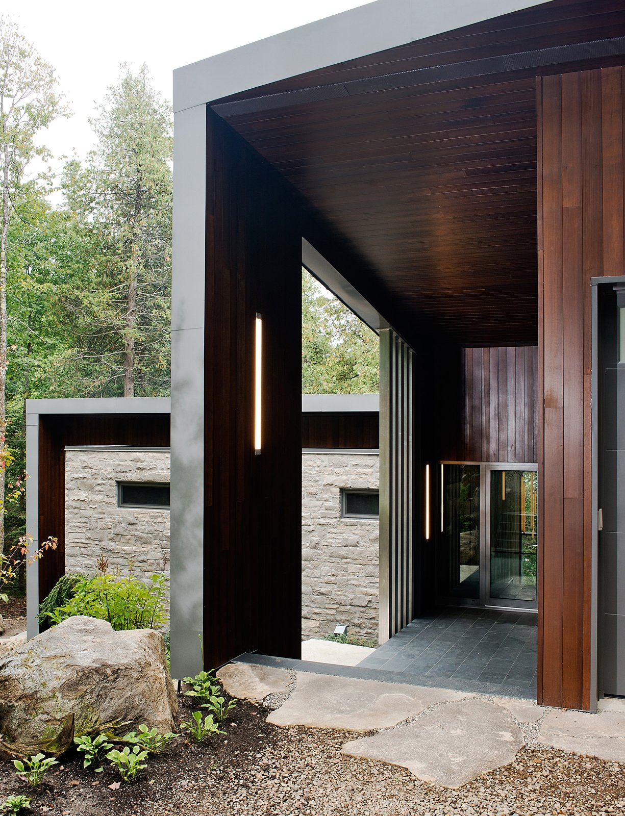 Exterior, Wood Siding Material, Stone Siding Material, Metal Siding Material, and House Building Type Tremblay chose materials that would reflect the natural setting, like the Polylam-C cedar siding from Prorez, used at the home's entrance. The exterior floor finish is Montauk grey slate.  Chalet Lac Gate by Kelly Dawson