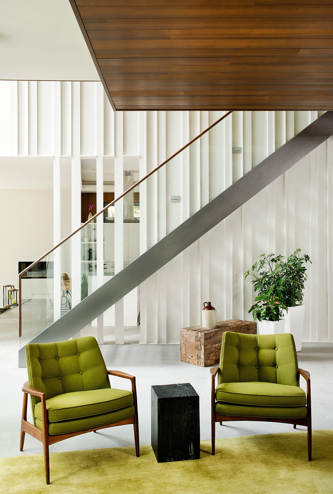Living Room, Concrete Floor, Rug Floor, Chair, and Stools Raw wood planks were painted white and fitted next to a staircase and banister by Bättig Design. Matching chairs by Thayer Coggin sit atop a Crate and Barrel rug.  Chalet Lac Gate by Kelly Dawson
