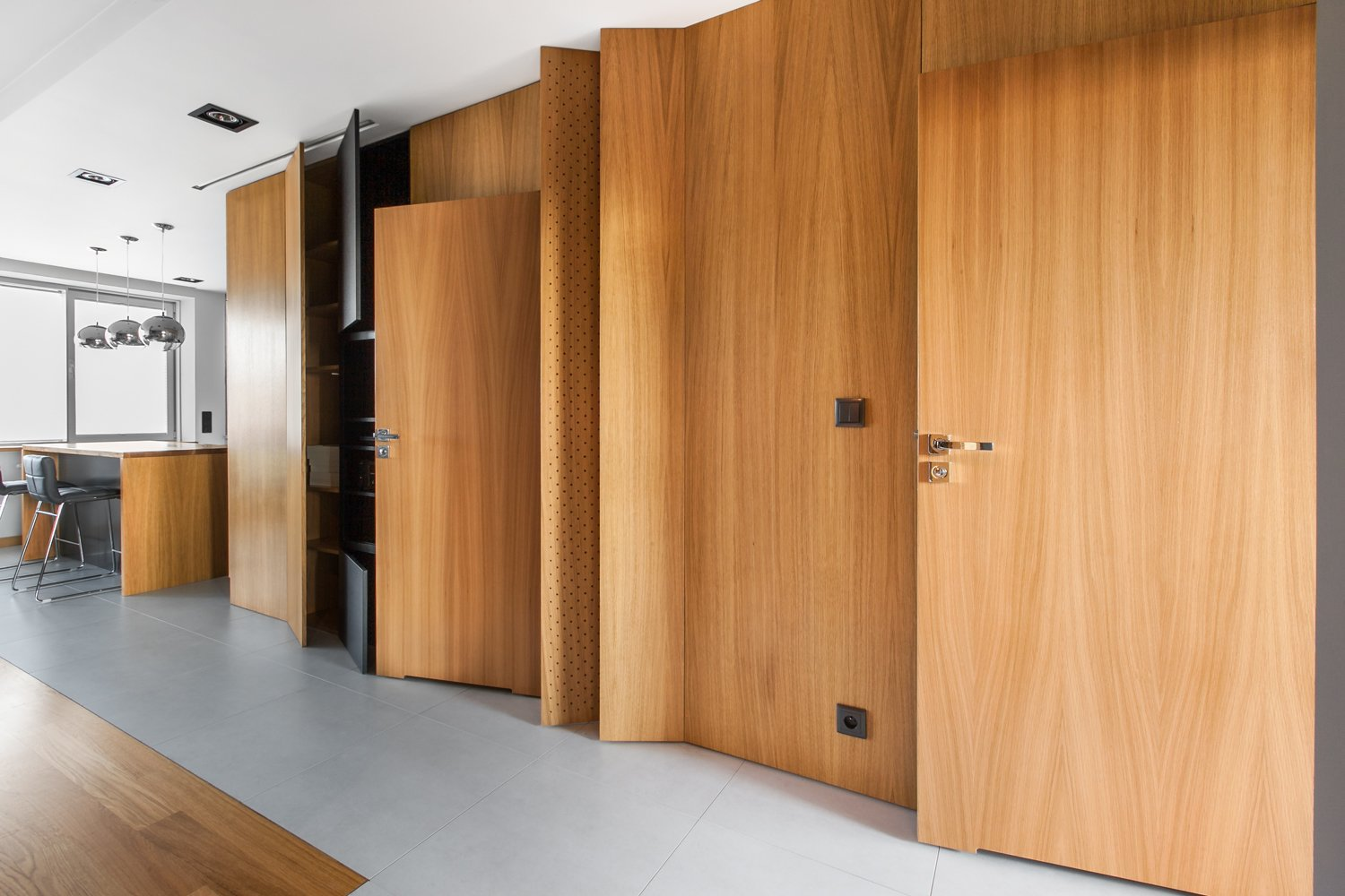 """Storage Room and Closet Storage Type The apartment's entryway features a hidden storage wall and media console.  Search """"five open decks"""" from An Open-Plan Apartment Renovation in Poland"""
