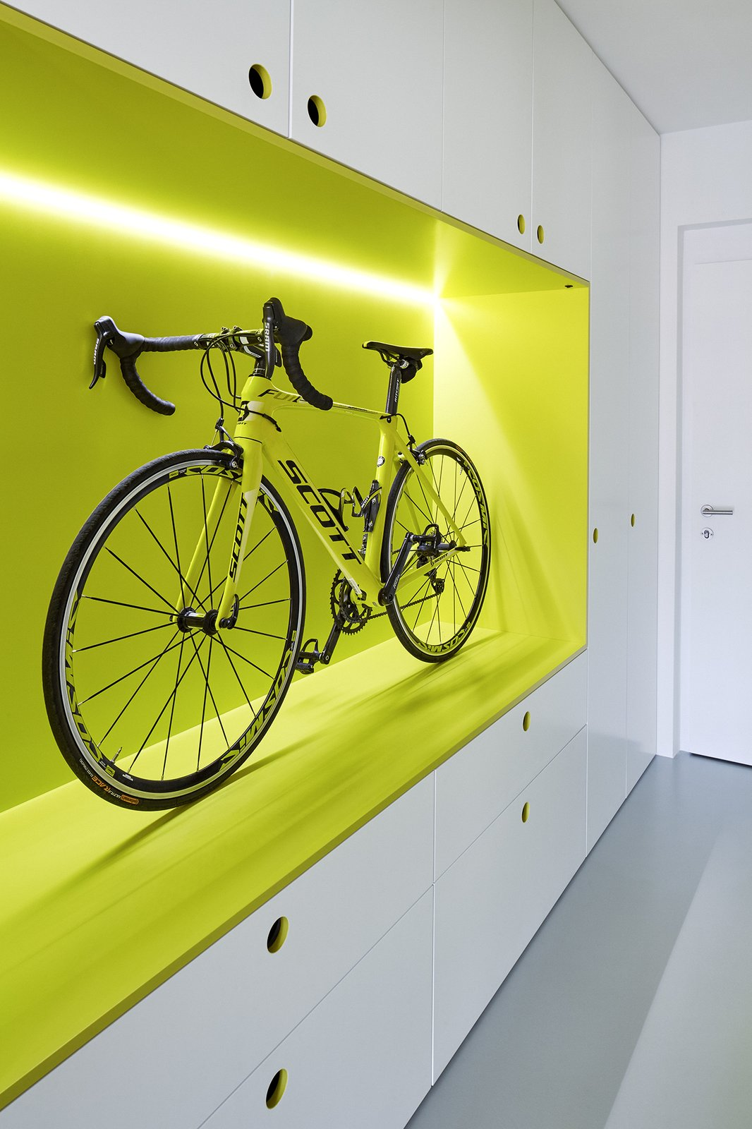 The owner is an avid cyclist; the guest apartment's hallway entrance features this unique storage space for his roadbike. Old damaged floors were replaced with a durable polyurethane coating.  Strikingly Minimal by Zachary Edelson