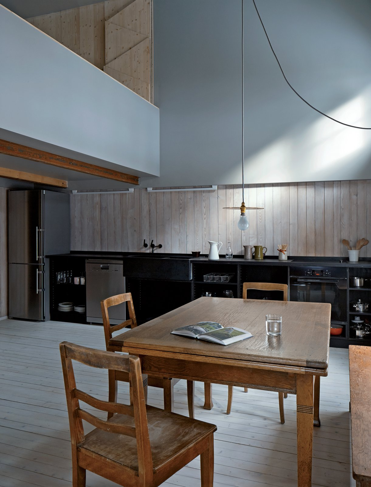 Among the furnishings that came with the house are the table and chairs in the kitchen–dining area. The pendant is by 6a for Izé.  Photo 2 of 12 in A Sliced-Up House Comes Together Again