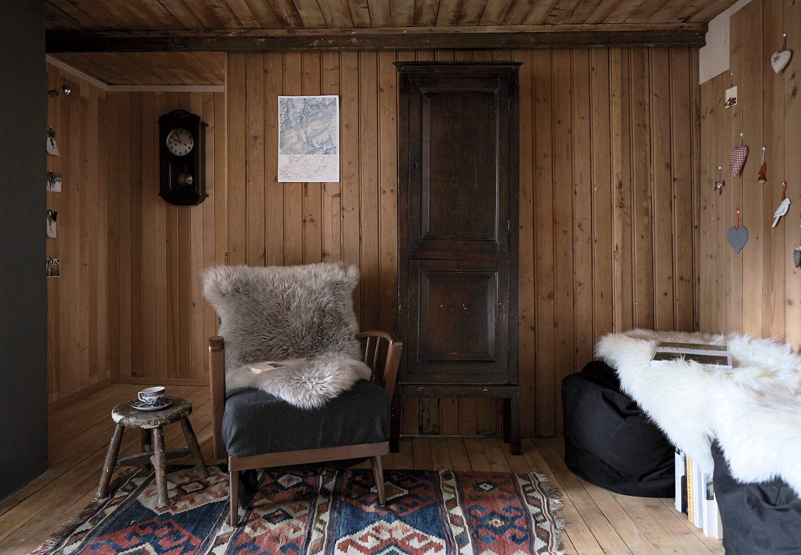 Original wood paneling envelops the stübli, a small, cozy room Tuckey decorated with a vintage cocktail chair from Poland, IKEA beanbags, architectural monographs, and a family heirloom rug.  Photo 12 of 12 in A Sliced-Up House Comes Together Again