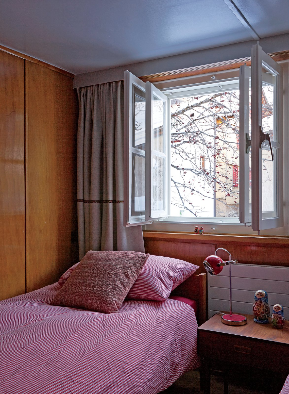 One of the daughters' rooms has a Danish rosewood bed and side table from Modernistiks. Tuckey found the 1970s red enamel-and-chrome lamp at Golborne Road market in London. Double windows help keep the Alpine winter chill at bay.  Photo 4 of 12 in A Sliced-Up House Comes Together Again