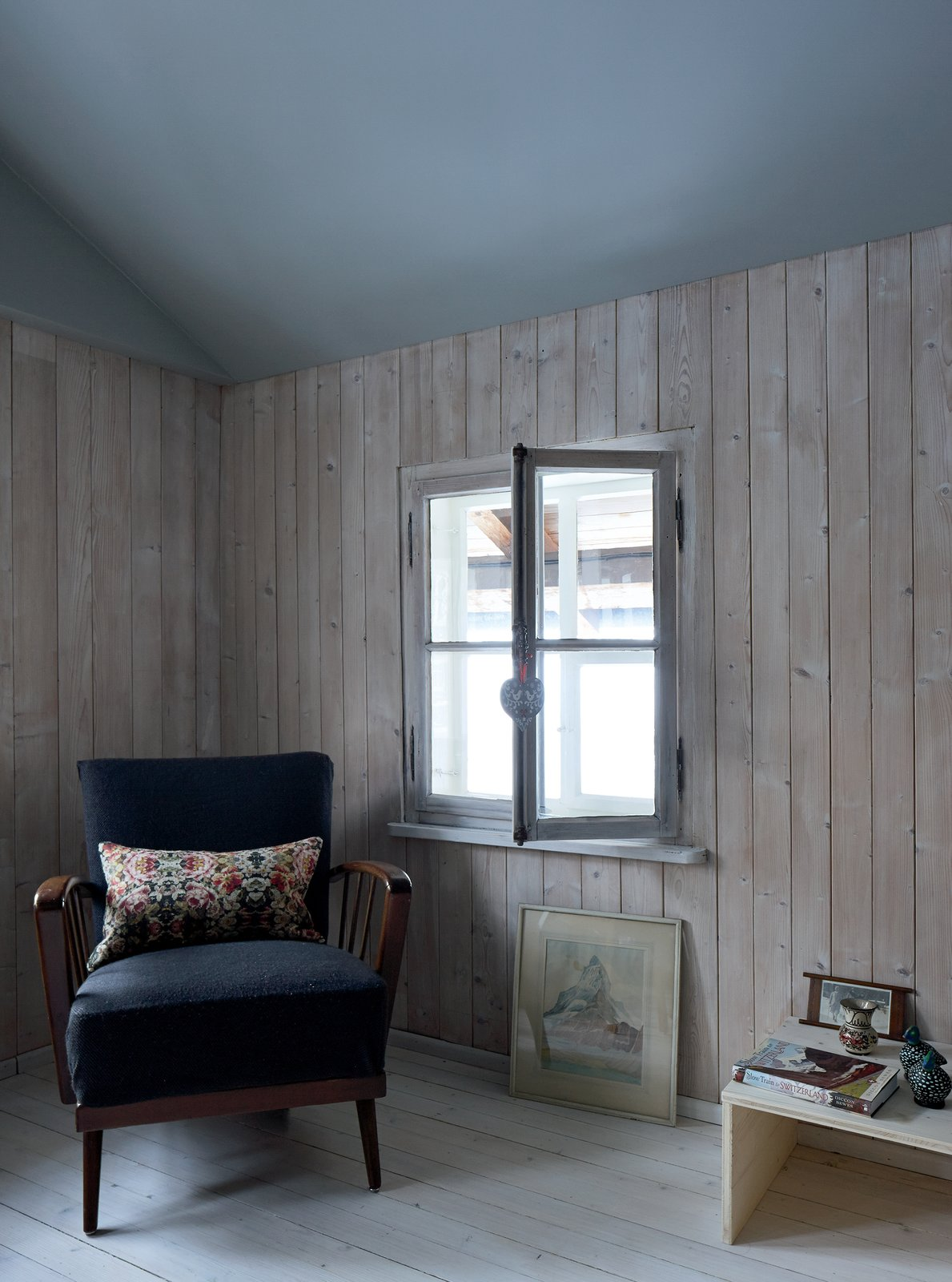 "Tuckey borrowed space from the former attic to create one open living space with a ceiling that complements the pine. ""I think it's important to have a small space, a medium space, and a big space in every project,"" he says.  Photo 6 of 12 in A Sliced-Up House Comes Together Again"