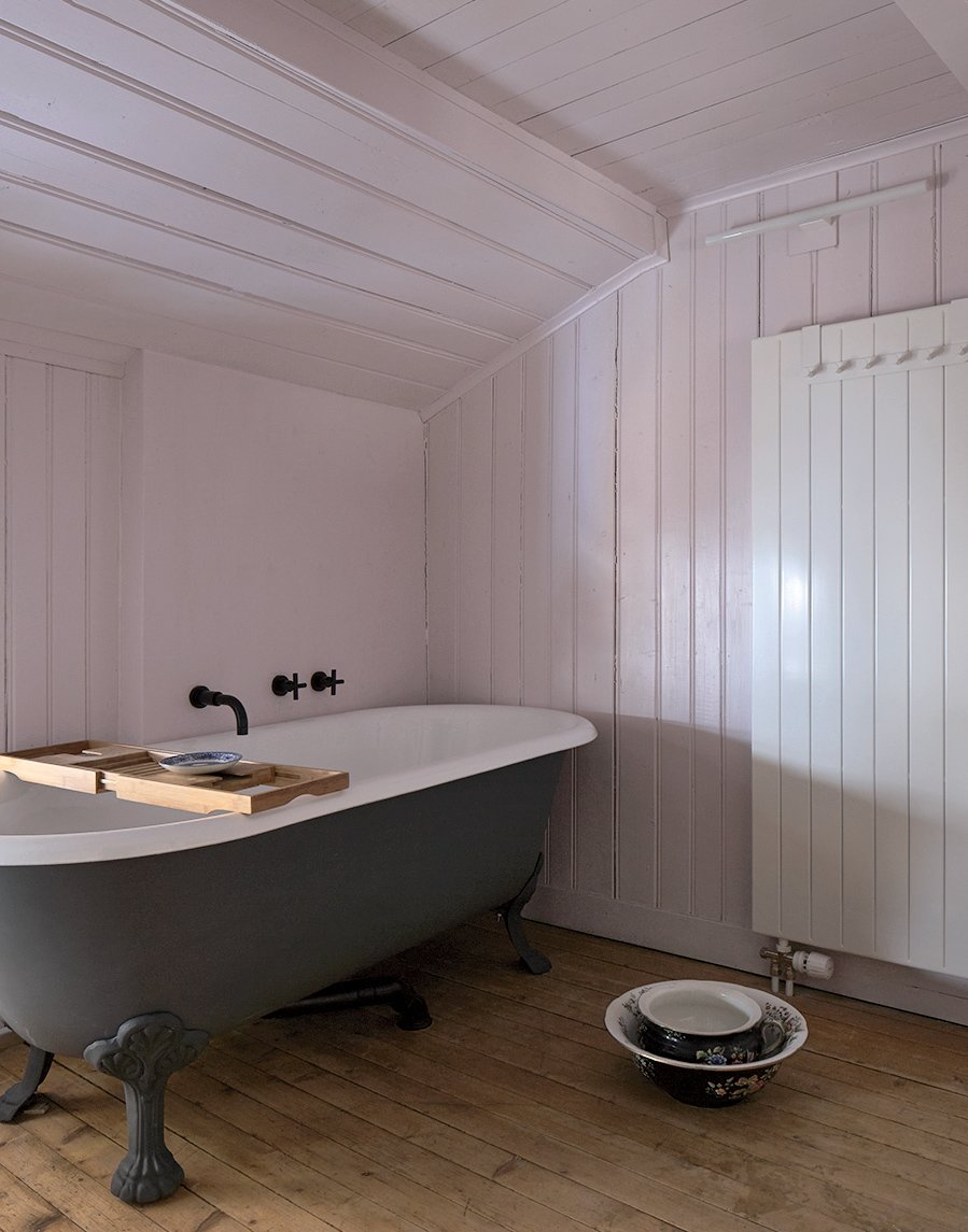 """A new coat of glazing (and a bit of a modern paint job on the exterior) brings a clawfoot bathtub back to life.  Search """"how bathrooms small spaces"""" from A Sliced-Up House Comes Together Again"""