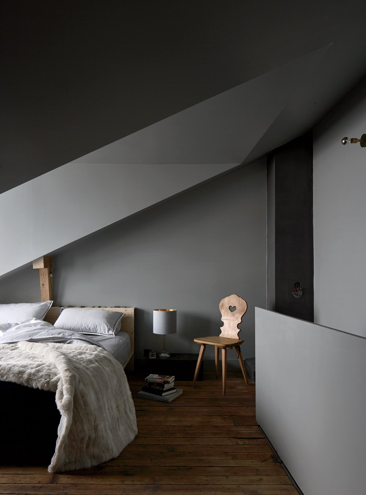 Like the stübli, the top-floor bedroom is meant to be moody. Tuckey designed the bed, the brass wall light is by John Glew Architects, and the chair is another piece inherited from the previous owners, a couple who lived there for decades.  Photo 10 of 12 in A Sliced-Up House Comes Together Again