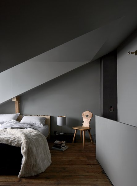 Like the stübli, the top-floor bedroom is meant to be moody. Tuckey designed the bed, the brass wall light is by John Glew Architects, and the chair is another piece inherited from the previous owners, a couple who lived there for decades.