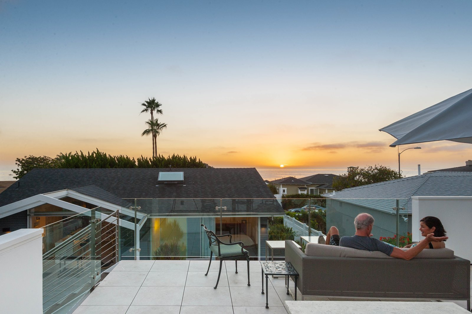 What this cottage lacks in size is made up for by stunning views of the ocean. The homeowners lounge on a Crate & Barrel sofa underneath a Hausers umbrella.  City Homes with Astounding Views by Luke Hopping from A California Cottage Renovated for Easy Indoor-Outdoor Living