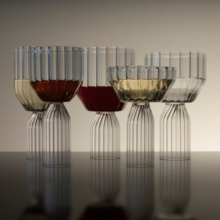 Designed by Felicia Ferrone, the Margot Collection presents a contemporary interpretation of cut glass. Handcrafted by master glassblowers in the Czech Republic, the Margot Collection is created from fluted Borosilicate glass to allow for the pieces to function in a range of temperatures. It includes a white wine glass, red wine glass, water goblet, champagne coupe, and dessert goblet, all sold as a set of two.