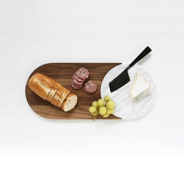 The Duo Serving Tray is a sophisticated serving piece comprised of rich walnut wood and elegant Carrara marble. Inspired by materials and shaped used in Bower NYC's furniture line, the Duo features a marble circle that perfectly nests into the walnut board, creating a complete, unified form. Both of the materials used in the tray are ideal for preparing and serving food, and can be separated into two pieces for different functions. The walnut section can be used for cutting bread and serving crackers and fruit, while the marble circle can be used for serving cheeses. The marble component can also be used as a trivet.