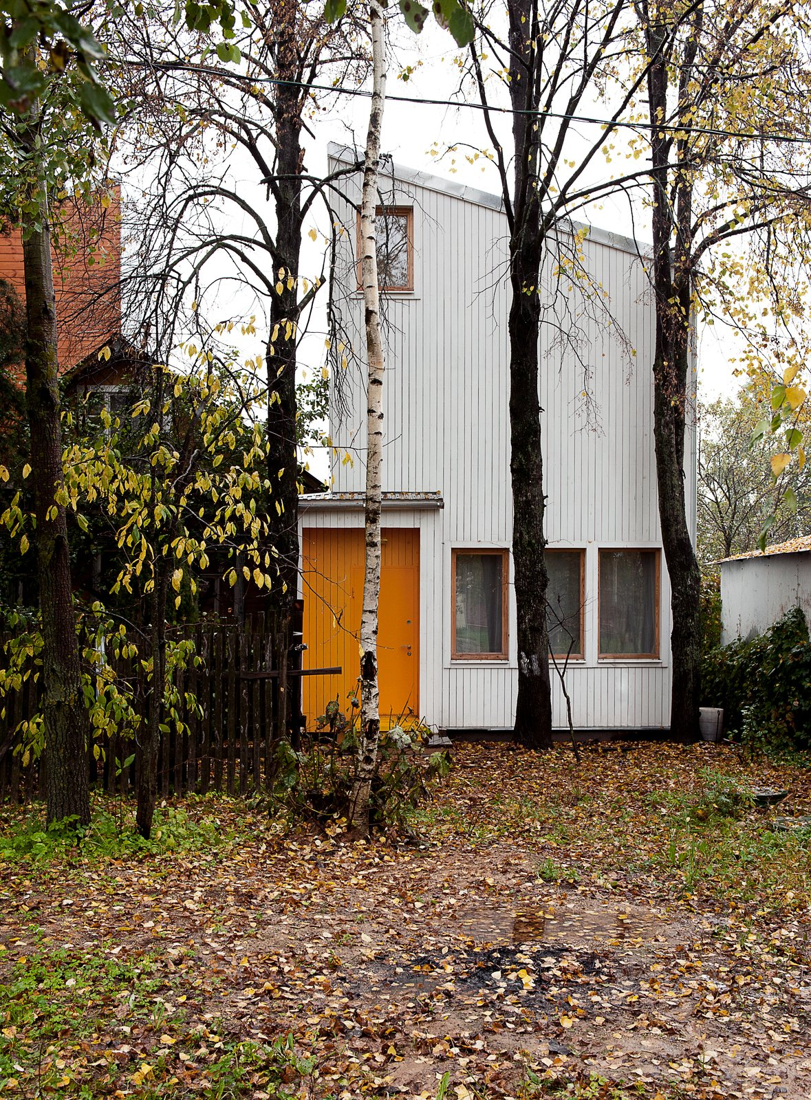"""""""Our goal was to construct a house with the lowest possible budget, while ensuring comfort and efficiency for the residents inside,"""" says Sergey Kolchin, founder of Le Atelier. The architects accented the home's front door by painting it yellow, harmonizing the structure with the surrounding forest.  A Compact Home in Moscow Built on the Lowest Possible Budget by Tiffany Jow"""