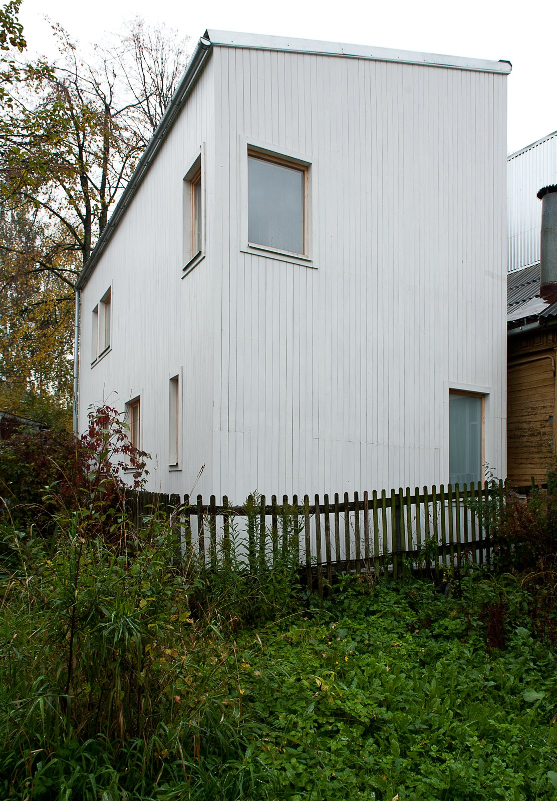 Placed throughout the home's slatted wood exterior, windows are positioned to allow for the most attractive views and ample natural light. The sloped roof design was chosen for its minimal cost, and for its ability to redirect snow away from a neighboring residence.  A Compact Home in Moscow Built on the Lowest Possible Budget by Tiffany Jow
