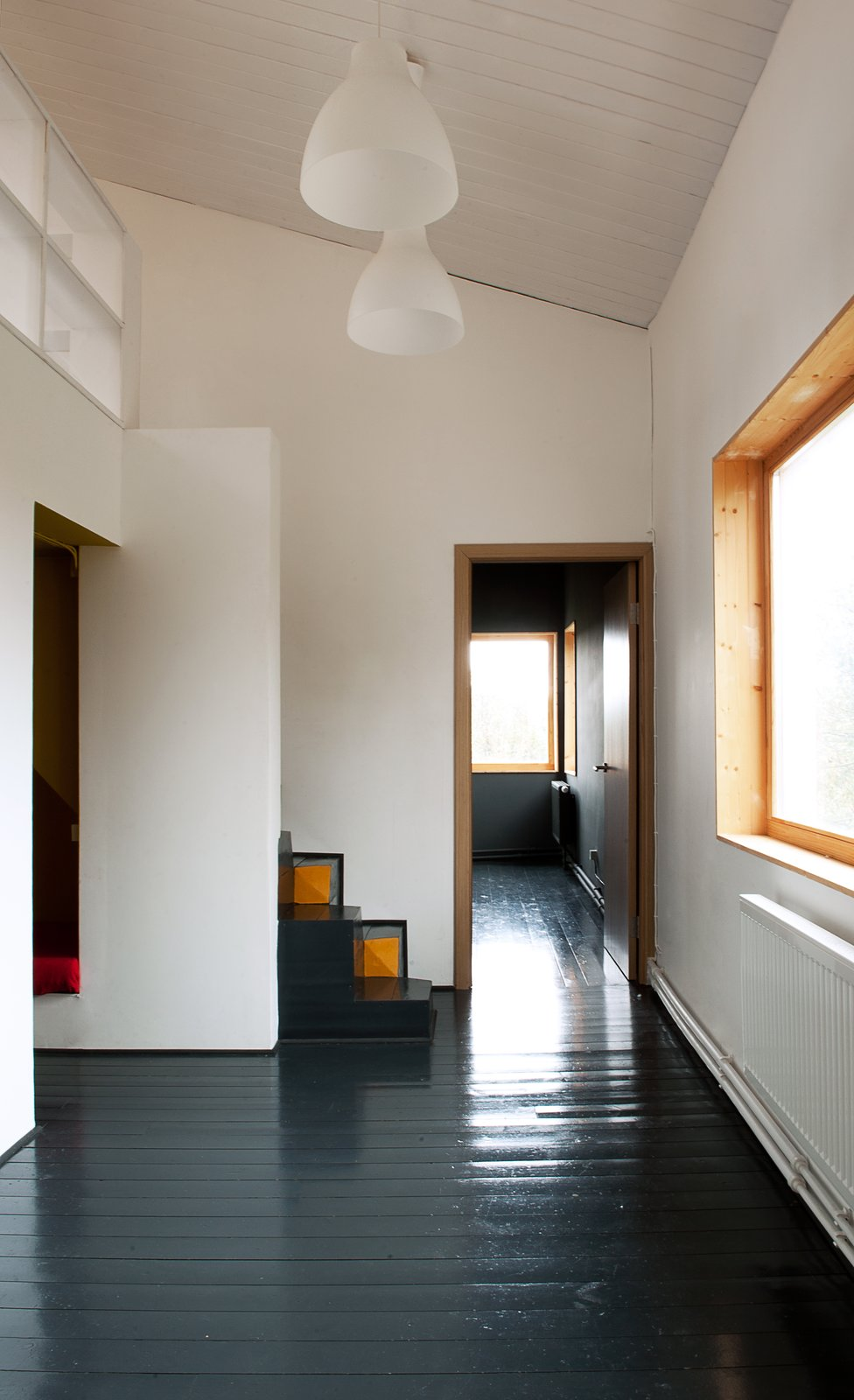 A pair of lights from IKEA hang above the first floor, which houses the living room, kitchen, and bathroom. Pine floors, painted black, run throughout the residence.  190+ Best Modern Staircase Ideas from A Compact Home in Moscow Built on the Lowest Possible Budget