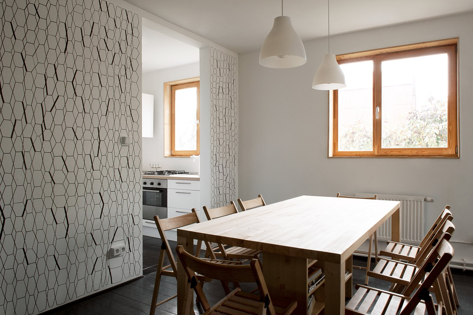 Chairs and lights from IKEA accompany a custom dining table, which incorporates shelving and storage space underneath.  A Compact Home in Moscow Built on the Lowest Possible Budget by Tiffany Jow