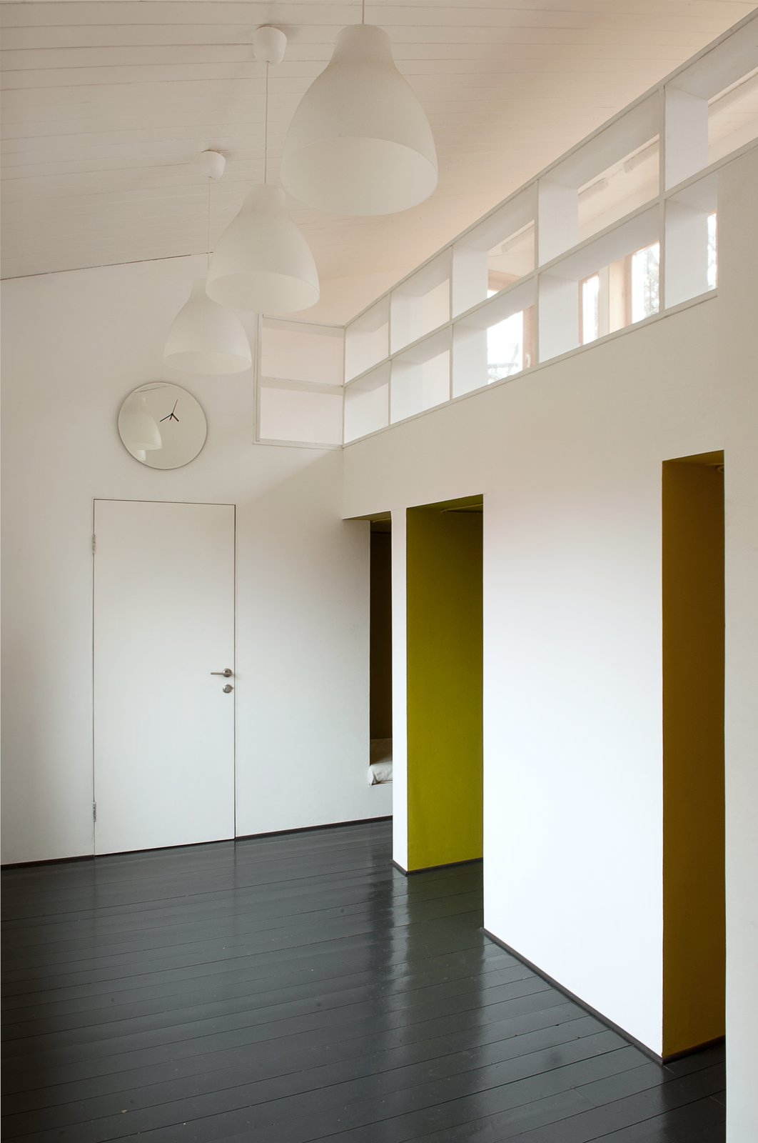 """Inspired by """"polati,"""" a sleeping loft that featured prominently in traditional Russian homes, Le Atelier created a series of tiny bedrooms that connect to a playroom with a study upstairs. A clock and lights from IKEA blend into the room's simple color palette.  A Compact Home in Moscow Built on the Lowest Possible Budget by Tiffany Jow"""