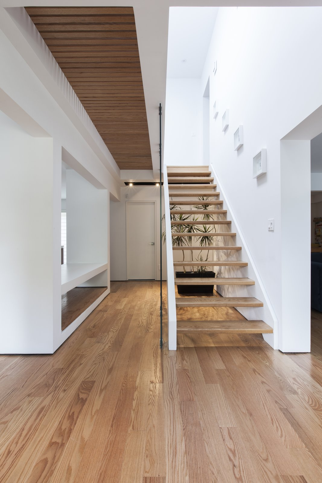 Staircase and Wood Tread A staircase forms the core of the 1,800-square-foot home, with a symmetrical alcove on either side. The steps, hardwood floors, and slatted bridge on the second floor are made of white oak, providing a rich contrast with its white walls.  190+ Best Modern Staircase Ideas from An Airy Toronto Home with Incredible Double-Height Rooms