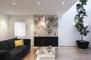 A large slab of marble doubles as an artwork in the living room, which is accented with an E23 sofa. Aliabadi used leftover pieces of the marble to create a custom coffee table.