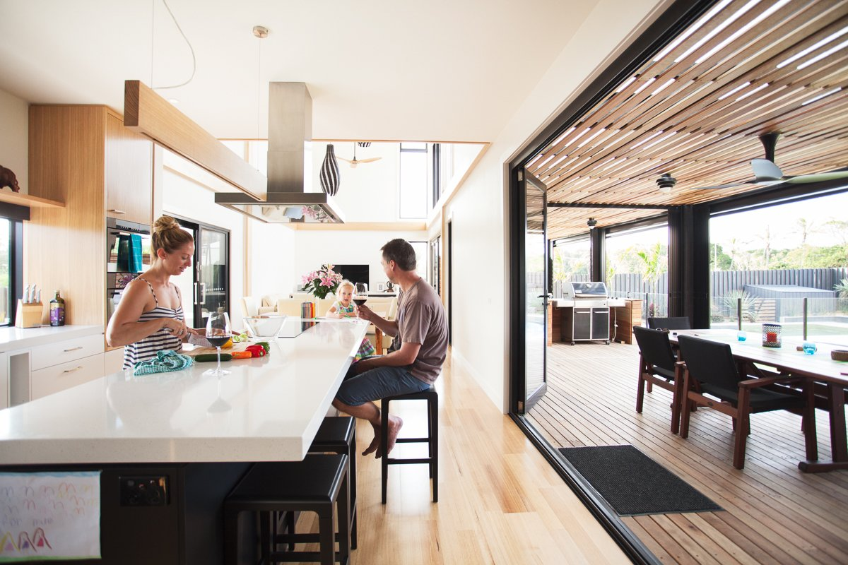 Kitchen, Wood Cabinet, Light Hardwood Floor, and Ceiling Lighting The residents, a family of three, spread out over the house's four bedrooms and two living areas.  Photo 8 of 8 in A Modular Beach Home in Australia Allows One Family to Keep an Eye on the Surf from Outdoor Dining Areas We Love October 19, 2015